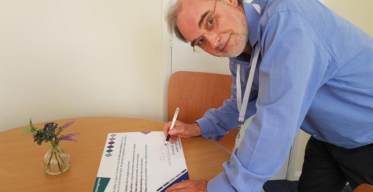 David N Jones, Chair of Healthwatch Northamptonshire, signing the wellbeing pledge.