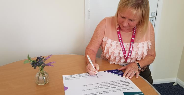 Kate Holt, CEO of Healthwatch Northamptonshire and Connected Together CIC, signing the wellbeing pledge.