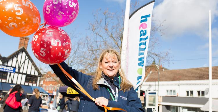 Healthwatch staff member holding balloons at a community event
