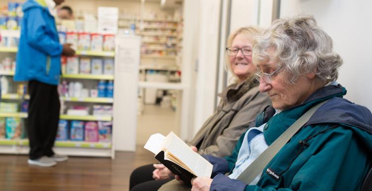 Two elderly women sitting in a pharmacy waiting for their prescription