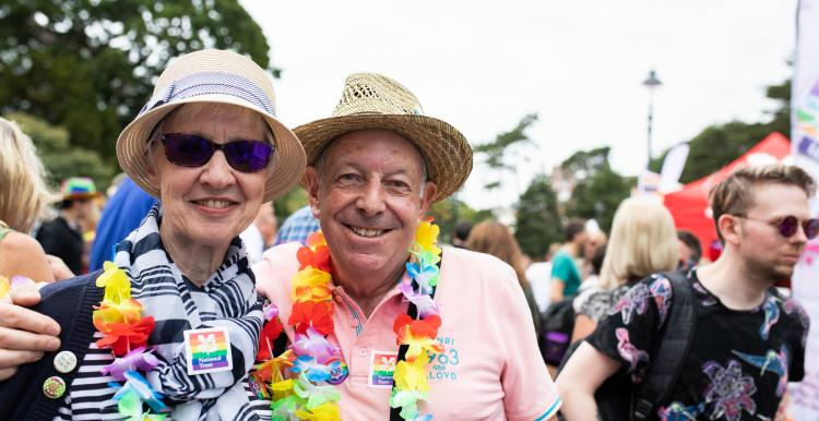 Older people smiling at camera at pride event