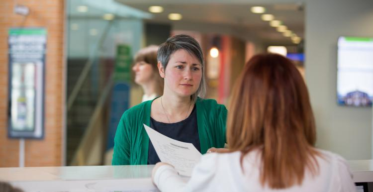 Woman speaking to receptionist
