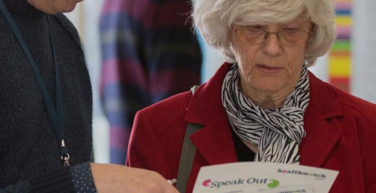 People speaking looking at leaflet