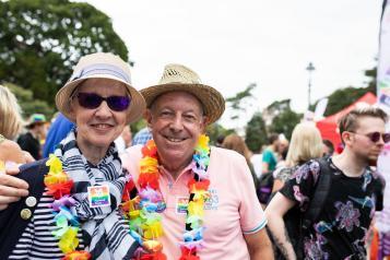 Older people smiling at camera at pride event