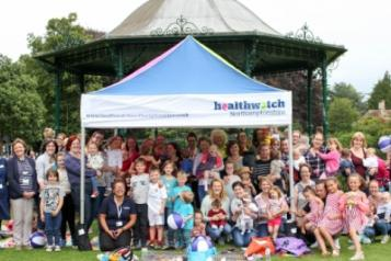 a group picture of all the attendees of the breastfeeding picnic under a Healthwatch gazebo