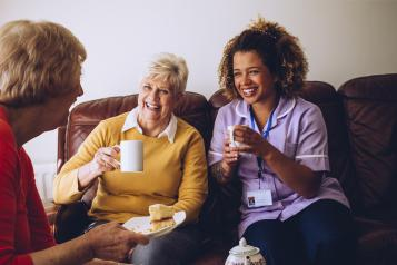 two old women in a care home laughing with their nurse