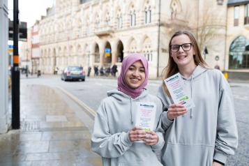 Two young female volunteers holding Healthwatch leaflets
