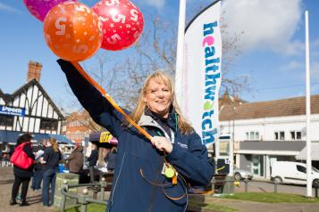 Healthwatch employee holding balloons infront of a Healthwatch sign