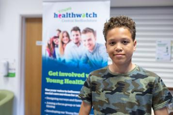 Young person in front of Healthwatch banner smiling