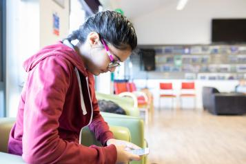 Young person using phone in waiting room