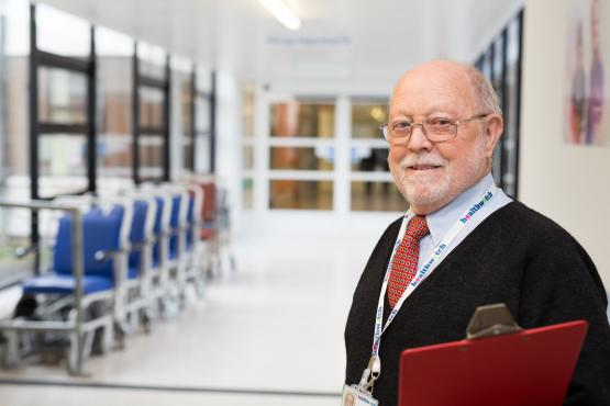 Older male Healthwatch volunteer with clipboard at hospital