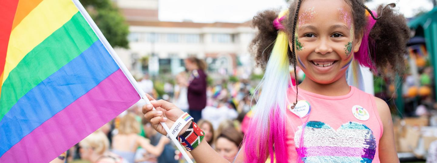 Young girl holding rainbow flag at pride