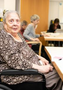 Older women wheelchair user at table with pen
